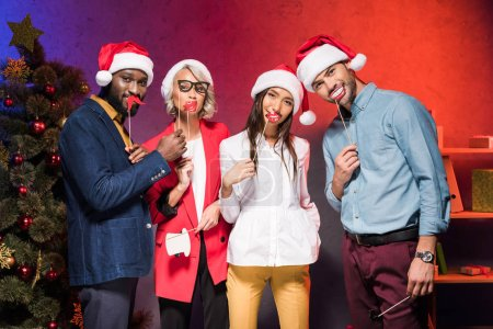 multiethnic managers holding lips and glasses on sticks at new year corporate party