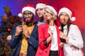 multicultural businesspeople holding lips and glasses on sticks at new year corporate party and looking away