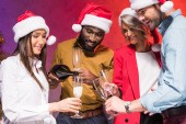 african american businessman pouring champagne into colleagues glasses at new year corporate party