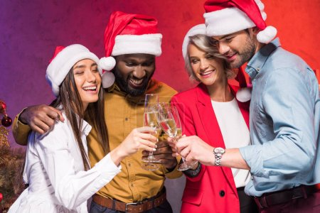 young multicultural businesspeople clinking with glasses of champagne at new year corporate party