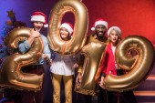 excited multicultural businesspeople holding 2019 balloons at new year corporate party