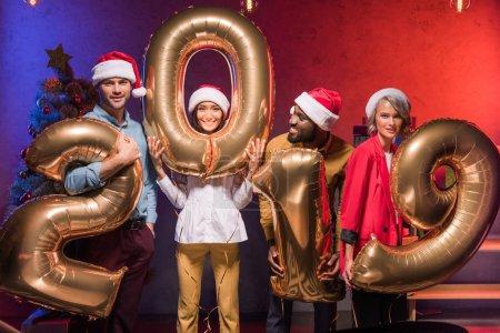 Foto de Jóvenes directivos multiculturales sosteniendo globos 2019 en fiesta corporativa de fin de año - Imagen libre de derechos