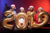 smiling multiethnic businesspeople in santa hats holding 2019 balloons at new year corporate party