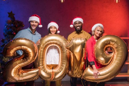 happy multiethnic businesspeople in santa hats holding 2019 balloons at new year corporate party