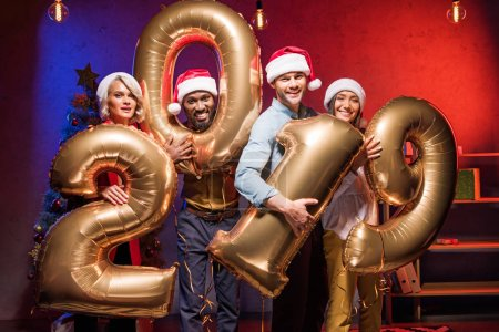 Photo for Young multicultural businesspeople in santa hats holding 2019 balloons at new year corporate party - Royalty Free Image