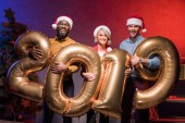 happy multicultural businesspeople holding 2019 balloons at new year corporate party