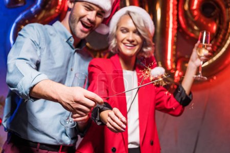 Photo for Young businesspeople in santa hats holding christmas sparklers at new year corporate party - Royalty Free Image