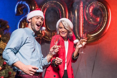 Foto de Empresarios jóvenes con sombreros de santa que se divierten en fiesta corporativa de fin de año - Imagen libre de derechos