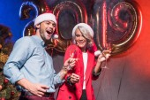 young businesspeople in santa hats having fun at new year corporate party