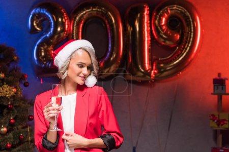Photo pour Belle femme d'affaires caucasien chapeau de santa tenant le verre de champagne à entreprise fête de nouvel an - image libre de droit
