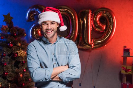 handsome businessman in santa hat standing with crossed arms at new year corporate party