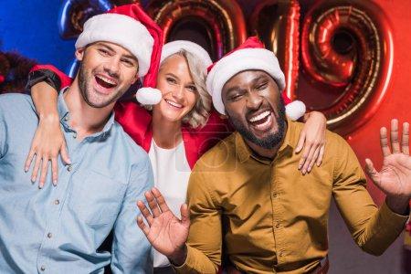 Foto de Empresarios multiculturales felizes mirando a cámara en fiesta corporativa de fin de año - Imagen libre de derechos