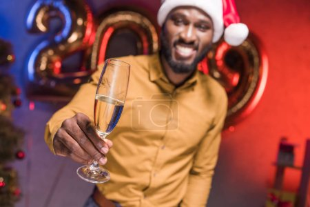 Photo for Happy african american businessman in santa hat showing glass of champagne at new year corporate party - Royalty Free Image