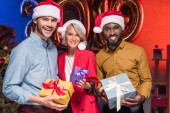 happy multicultural businesspeople in santa hats holding gift boxes at new year corporate party