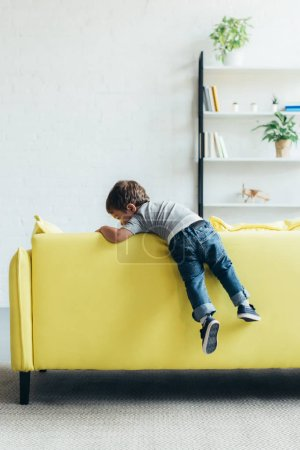 little boy climbing up on yellow sofa at home
