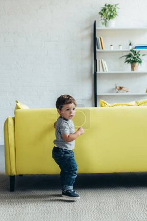 little boy playing near yellow sofa at home