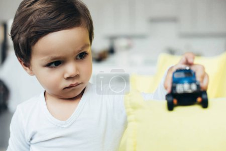selective focus of boy playing with toy car