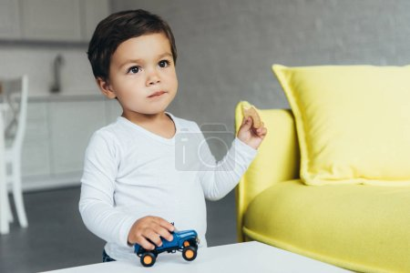 Photo for Adorable boy playing with toy car and eating cookie - Royalty Free Image