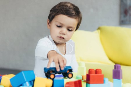 adorable boy playing with toy car on colorful constructor blocks