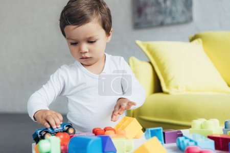 cute kid playing with toy car and colorful constructor blocks at home