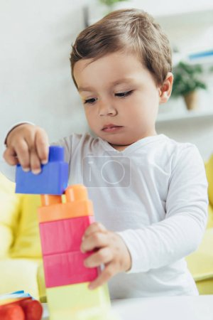 toddler playing with colorful constructor blocks at home