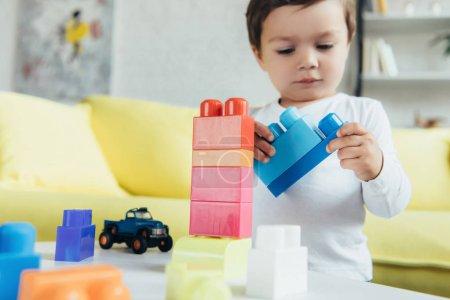 Foto de Hijo varón jugando con colorido juguete y constructor del coche en casa - Imagen libre de derechos