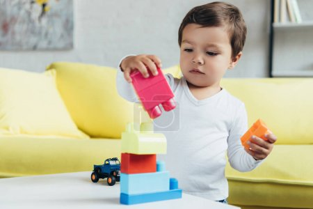 cute toddler playing with colorful constructor blocks on table