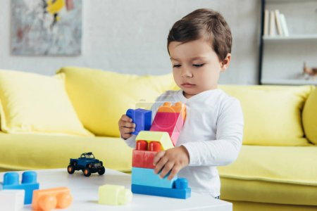 little boy playing with colorful constructor blocks and toy car at home