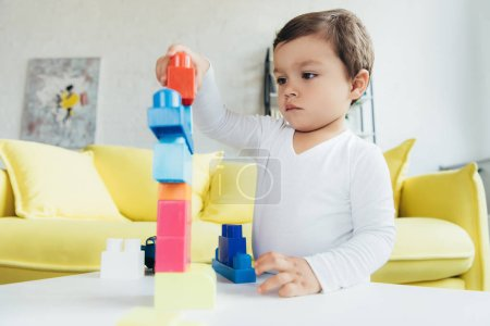 cute kid playing with colorful constructor blocks on table at home