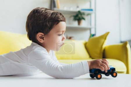 Photo for Adorable little boy playing with toy car at home - Royalty Free Image