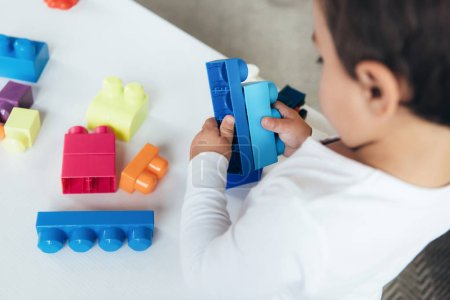 cropped view of boy playing with colorful constructor blocks