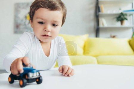 Foto de Adorable niño jugando con coches de juguete azul en casa - Imagen libre de derechos