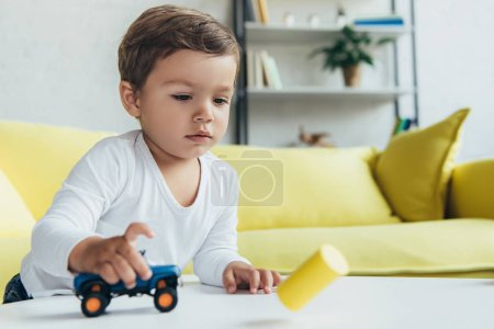 Photo for Adorable kid playing with blue toy car at home - Royalty Free Image