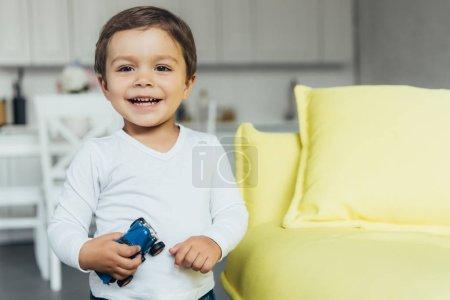 Foto de Adorable muchacho sonriente con coche de juguete en casa - Imagen libre de derechos