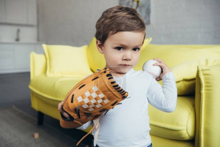 cute toddler playing with baseball glove and ball at home