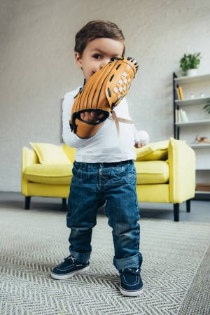 toddler playing with baseball glove and ball at home