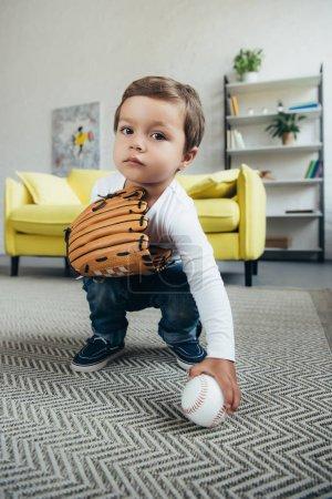 Photo pour Adorable enfant qui joue avec le gant de baseball et de balle à la maison - image libre de droit