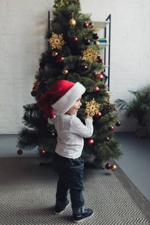 Photo for Cute smiling boy in santa hat pointing at christmas tree - Royalty Free Image