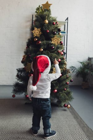 back view of male child in santa hat pointing at christmas tree