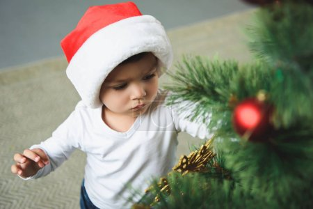 cute boy in red santa hat decorating christmas tree