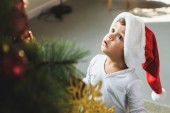 adorable little kid in santa hat looking up at christmas tree