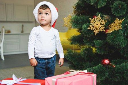 Photo pour Adorable petit enfant en bonnet de noel avec des coffrets-cadeaux près de sapin de Noël - image libre de droit