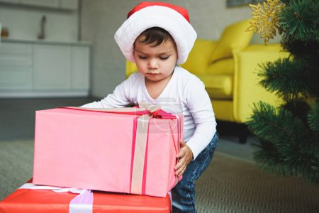 adorable boy in santa hat with gift boxes near christmas tree