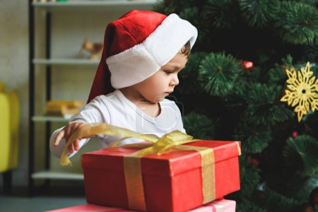 adorable toddler in santa hat with gifts near christmas tree