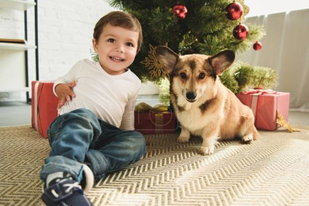 happy kid with welsh corgi dog sitting under christmas tree