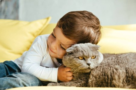 happy toddler hugging scottish fold cat on sofa at home