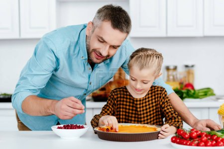 father and adorable little daughter decorating pumpkin pie for thanksgiving day