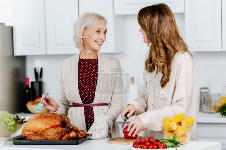 attractive adult daughter and senior mother cooking thanksgiving dinner together