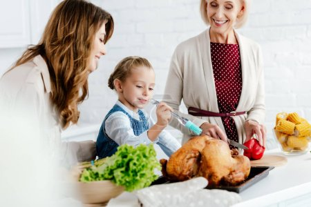 mother and grandmother preparing thanksgiving turkey with granddaughter
