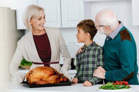 excited little kid with grandparents preparing thanksgiving turkey together at kitchen